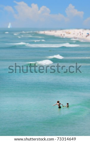 Vacationers swimming in pretty ocean
