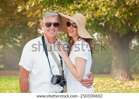 Vacationing couple against trees and meadow in the park - stock photo