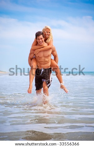 Vacationing couple running in the water at the beach - stock photo