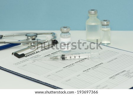 Vaccine vials with syringe and stethoscope on patient chart.. - stock photo