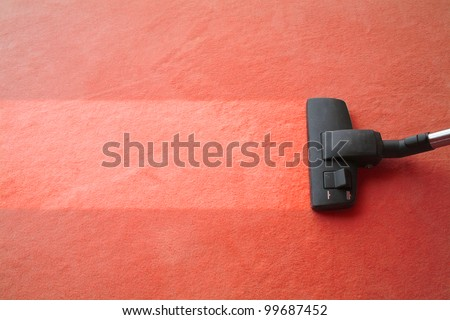 Vacuum cleaner cleans carpet, with space for text message, advertising, red - stock photo