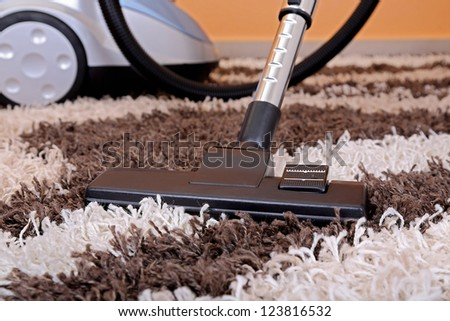 vacuum cleaner on fluffy carpet - stock photo