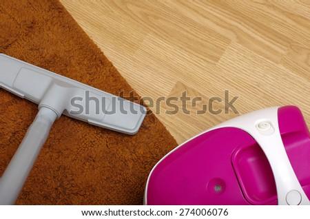 vacuum cleaner over wooden floor - stock photo