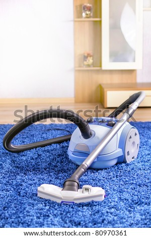 Vacuum cleaner stand  on blue carpet - stock photo