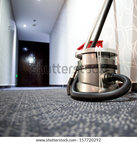 vacuum cleaner stands in the hotel corridor. - stock photo