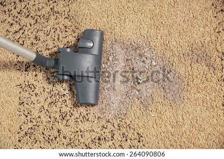 Vacuum cleaning dirt on a carpet - stock photo