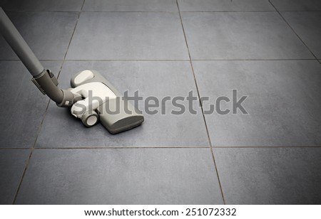 vacuuming flooring in kitchen - stock photo