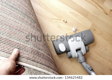 Vacuuming under carpet - stock photo