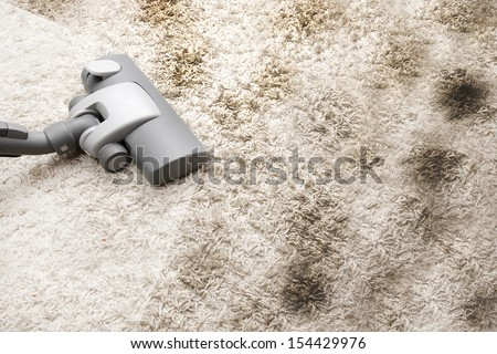 Vacuuming very dirty carpet in house - stock photo