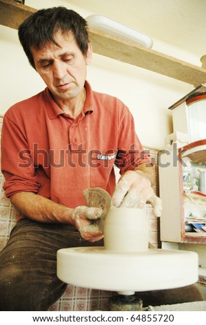 VADU CRISULUI, ROMANIA - CIRCA JULY: Potter works with clay to model a new vase in the traditional Vadu Crisului style, circa July, 2006 in Vadu Crisului, Romania