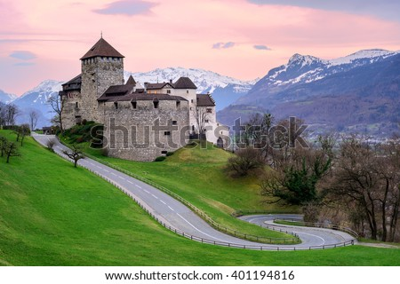 Vaduz Castle, the official residence of the Prince of Liechtenstein, with snow covered Alps mountains in background on sunset - stock photo