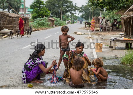 VAISHALI, INDIA - JULY 18 2016:Indian women wash clothes in street rural village on July 18, 2016 in Vaishali, India.