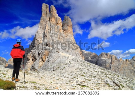 Vajolet towers scrutinized by a woman climber in sunny day, Catinaccio massif, Dolomite Alps, Italy - stock photo