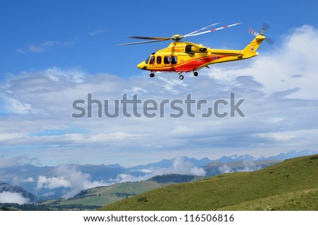 VAL DI FASSA, ITALY - AUGUST 16: Rescue helicopter from Trento Alpine Rescue Service flying at accident site on August 16, 2012 in Val di Fassa, Italy - stock photo