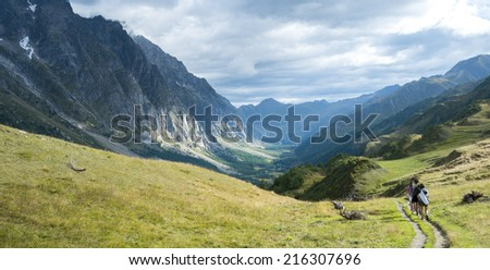VAL FERRET, ITALY - AUGUST 29: Hikers walking in Val Ferret in Italy, with overcast sky and rocky mountain range. The area is a stage of the Mont Blanc tour. September 29, 2014 in Val Ferret. - stock photo