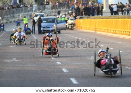 VALENCIA - NOVEMBER 27: Unidentified handicapped wheel chair hand-bikers participating in Valencias Marathon behind runners on November 27, 2011 in Valencia, Spain - stock photo