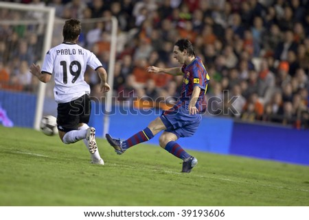 VALENCIA - OCTOBER 17 : Leo Messi (R) of Barcelona FC in action at Spanish soccer league match Valencia C.F. vs F.C. Barcelona at Mestalla Luis Casanova Stadium October 17, 2009 in Valencia. - stock photo