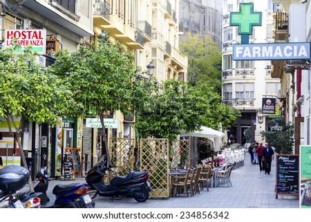 VALENCIA, SPAIN - APRIL 4 : one of the central streets in Valencia - tourists and Spanish walking by open cafe terraces and all kind of shops on April 4th, 2014 in Valencia, Spain - stock photo