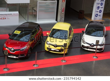 VALENCIA, SPAIN - DECEMBER 4, 2014:  A red Renault Captur, a yellow Renault Twingo and a white Renault Clio at the Valencia Automovil 2014 Car Show. Renault is the third biggest European automaker. - stock photo