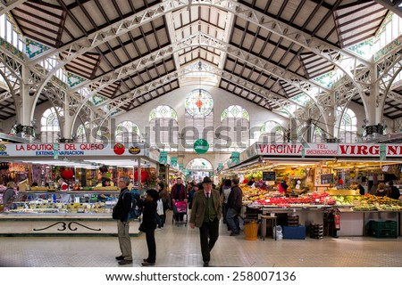 VALENCIA, SPAIN - FEBRUARY 17: Symmetrical composition of people shopping in the old central market, one of the most attractive and visited buildings, on February 17, 2015 in Valencia, Spain. - stock photo