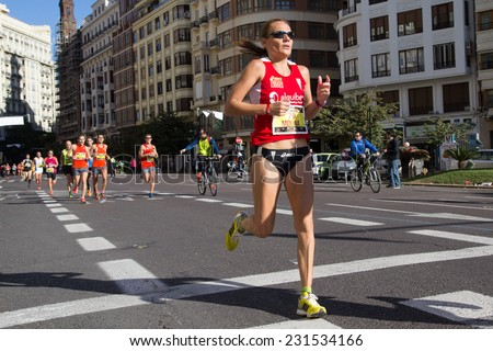 VALENCIA, SPAIN - NOVEMBER 16, 2014: Woman runner Bea Molina of Spain competes in the 2014 Valencia Marathon.  Molina was the first Spanish woman to cross the finish line with a time of 2:52:38. - stock photo