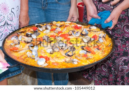 Valencian paella rice held by women - stock photo