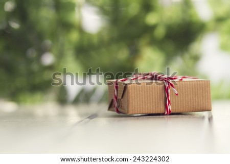 Valentine. A paper parcel wrapped tied. A gift box wrapped with paper kraft and tied with red & white baker's twine on a white wooden table. Vintage Style. - stock photo