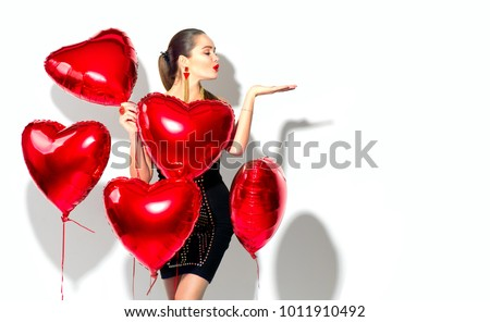 Valentine Beauty girl with red air balloon portrait pointing hand, isolated on background. Beautiful Happy Young woman presenting products. Holiday party, birthday. Joyful model