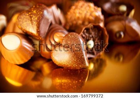 Valentine Chocolates. Assorted Chocolate Candies. Chocolate Sweets. Candy Border Design over Golden Background. Heart Shaped Chocolate - stock photo