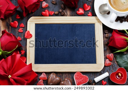 Valentine composition with coffee,  chalkboard and flowers on wooden background