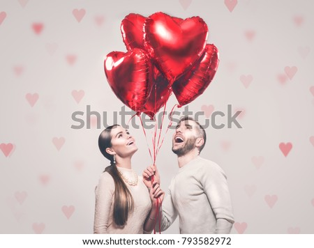 Valentine Couple. Portrait of Smiling Beauty Girl and her Handsome Boyfriend holding bunch of heart shaped air balloons and laughing. Happy Joyful Family. Love. Happy Valentine's Day