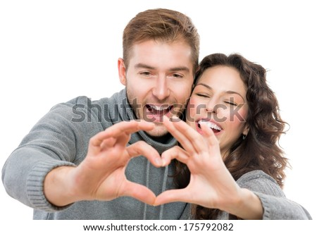 Valentine Couple. Portrait of Smiling Beauty Girl and her Handsome Boyfriend making shape of Heart by their Hands. Happy Joyful Family. Love Concept. Heart Sign. Laughing Happy Lovers. Valentines Day - stock photo
