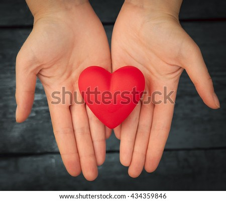 Valentine day. Red heart in the hands. Red heart on the dark boards. Valentine's Day. Heart pendant. Red heart. Space for text. Eighth of March. International Women's Day. Toned image. - stock photo
