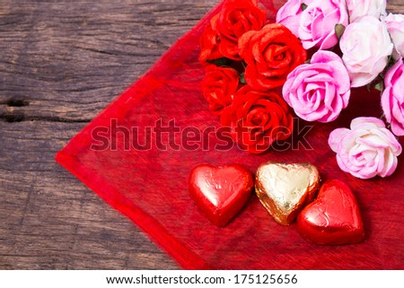 Valentine decoration, heart shaped chocolate and roses on wooden table top