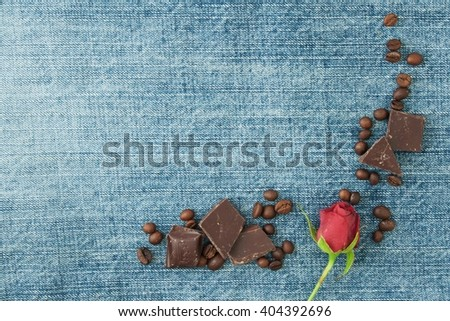 Valentine denim background, greeting card with original textile heart, coffee beans, little red rose and chokolates. Handmade concept. Your text on the card. - stock photo