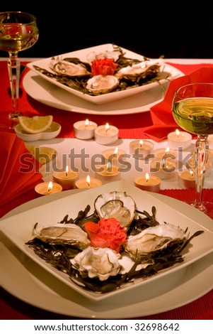 Valentine dinner setting with oysters and candles - stock photo