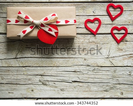 valentine gift box and red heart shapes, on wooden board - stock photo