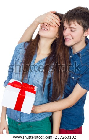 Valentine Gift. Happy Young beautiful Couple  isolated on a White background. Happy Man giving a gift to his Girlfriend. Holiday