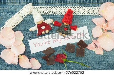 Valentine, greeting card with knitting couple in love, pieces of chocolate, little red rose and soft pink rose petals. Lettering You are my sweetie on the denim background. Handmade concept.
