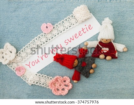 Valentine greeting card with pink and red hearts, knitting couple in love. Lettering Youâ??re my sweetie on the denim background - stock photo
