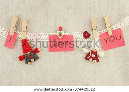 valentine, greeting card. Wooden pins, red and pink hearts, knitted loving couple man and woman, lettering I love you hanging on a clothesline. On the cloth background - stock photo