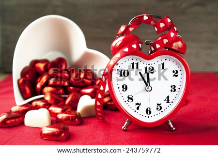 Valentine love heart shaped red clock with chocolates. Time for sweet love. Indoors closeup. - stock photo
