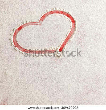 Valentine love red heart shape in snow on red background. Closeup.Christmas card.