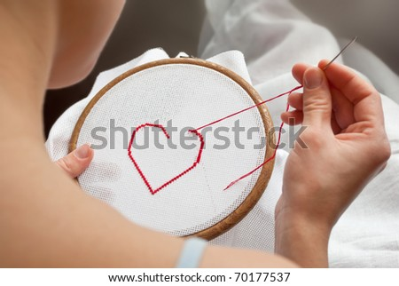 valentine red heart, being embroidered on canvas in tambour by female - stock photo