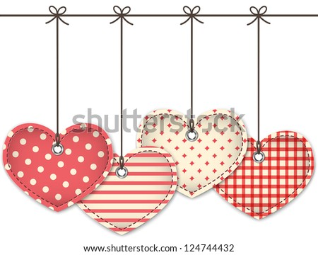 Valentine red textured hearts tied with bows hanging on white background