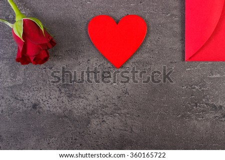 Valentine red wooden heart, rose and love letter in red envelope on structure of concrete, decoration for Valentines Day, copy space for text - stock photo