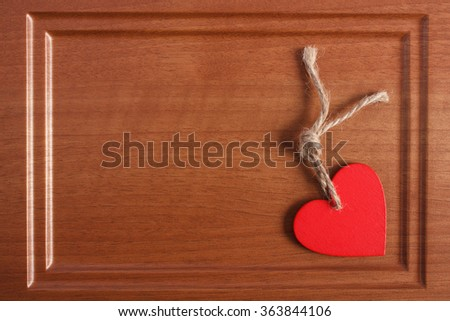 Valentine red wooden heart with twine on wooden background, decoration for Valentines Day, symbol of love, copy space for text - stock photo