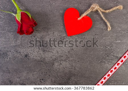 Valentine red wooden heart with twine, rose and ribbon on structure of concrete, decoration for Valentines Day, copy space for text - stock photo