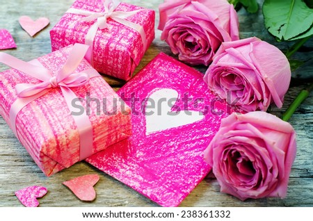 Valentine's background with gifts, flowers and card on a white wood background. tinting. selective focus on card - stock photo