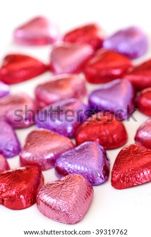 Valentine's chocolates wrapped in red and purple foil on white background - stock photo